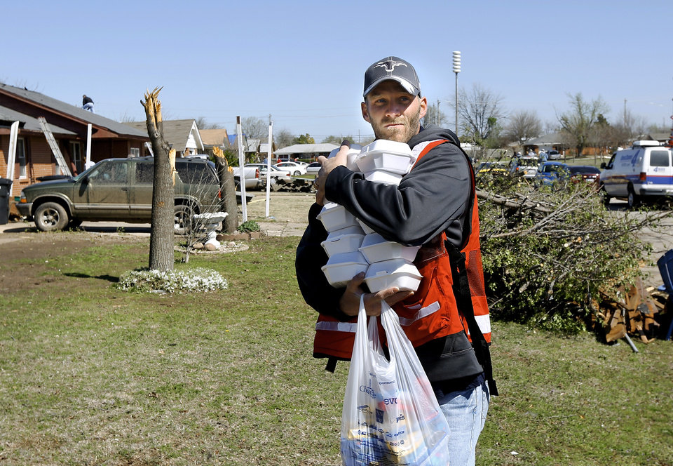 Photo - A Salvation Army volunteer carries boxed lunches into a neighborhood  between NW 5 and Main Street, and between Telephone Rd. and Santa Fe in Moore Thursday morning, March 26, 2015, the day after a tornado damaged homes and a school Wednesday evening. Photo by Jim Beckel, The Oklahoman