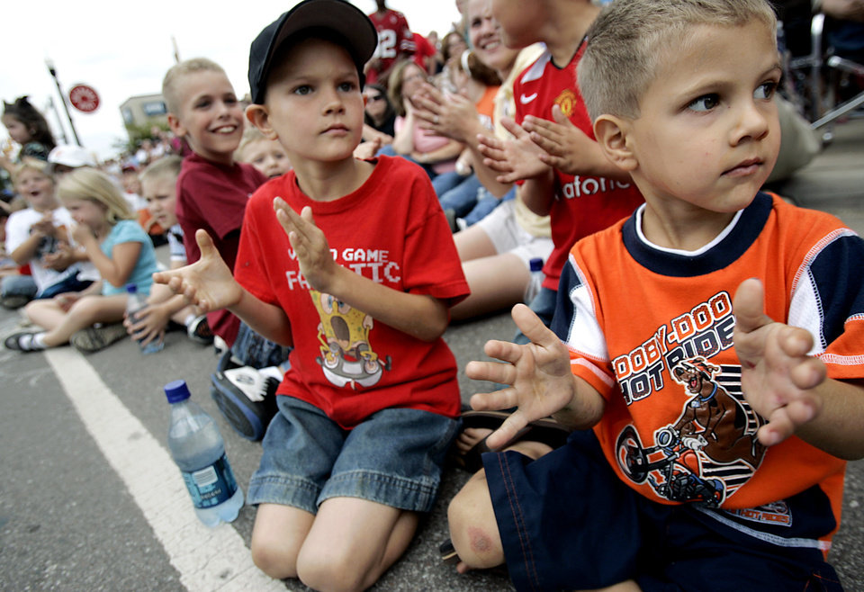 Photo - Tyler Prichard, age 7, (center) and Landon Prichard, age 4, of Moore (right) clap as a marching band passes during the Oklahoma Centennial Parade in Oklahoma City on Sunday, Oct. 14, 2007. By John Clanton, The Oklahoman