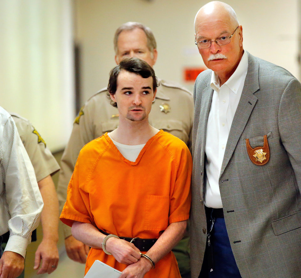 Photo - Alan Hruby is taken to the courtroom by Stephens County Sheriff Wayne McKinney, right, and his deputies. Murder defendant Alan J. Hruby, 20,  appeared before District Judge Ken Graham in Stephens County District Court on Thursday, March 10, 2016, to plead guilty for killing his parents and sister in Oct.  2014, at the family home in Duncan, Okla.  He was a freshman at the University of Oklahoma at the time of the murders. Stephens County District Attorney Jason Hicks accepted the plea agreement in which Alan agreed to accept three consecutive life sentences without parole. The defendant's father, John Hruby, mother, Tinker Hruby and sister, Katherine Hruby, died of gunshot wounds. Photo by Jim Beckel, The Oklahoman.