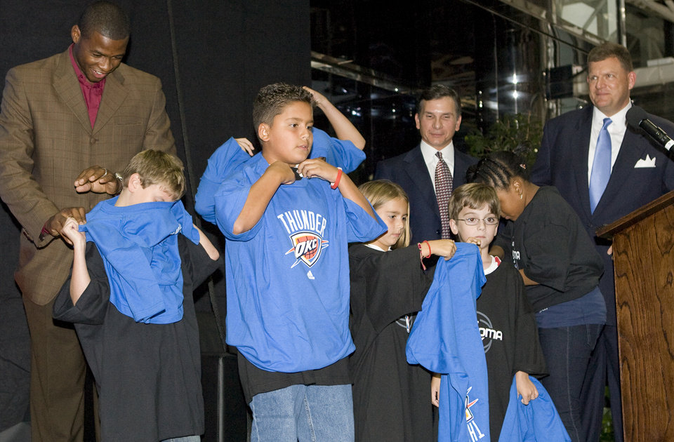 Photo - Children put on OKC Thunder shirts with help from player Desmond Mason, left, as Matt Pinto, middle, and team chairman Clay Bennett, right, watch during the unveiling of the Oklahoma City Thunder NBA team name at Leadership Square in downtown Oklahoma City, Wednesday, September 3, 2008. NATE BILLINGS, THE OKLAHOMAN