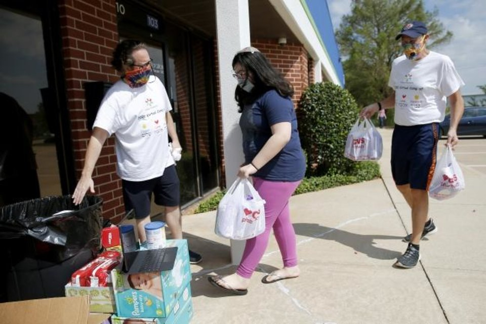 Photo -  Camp Chaverim Leadership In Training Assistant Directors Brian Stockton, left, and Jeff Gross meet participant Gracia Mejia-Jacobson, 11, as she drops off baby items outside the Jewish Federation of Greater Oklahoma City during the camp's drive-thru baby shower to benefit the Infant Crisis Center. [Bryan Terry/The Oklahoman]