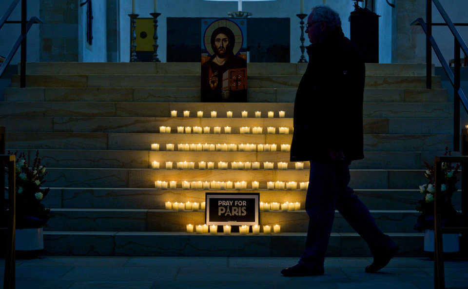 Photo - A man passes candles placed  for t victims of the Paris attacks Friday night,   in front of the Hildesheim cathedral in Hildesheim northern Germany, Saturday, Nov. 14, 2015.  French President Francois Hollande said more than 120 people died Friday night in shootings at Paris cafes, suicide bombings near France's national stadium and a hostage-taking slaughter inside a concert hall. (Peter Steffen/dpa via AP)