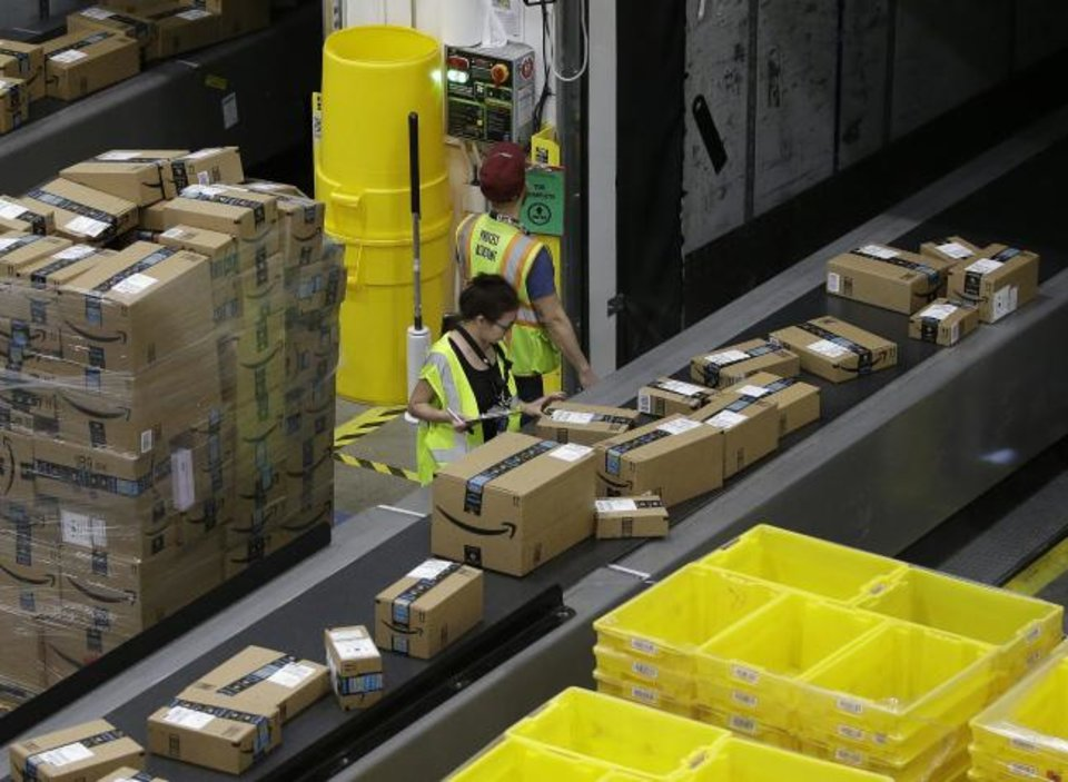 Photo -  Packages move down a conveyor system were they are directed to the proper shipping area at the new Amazon Fulfillment Center in Sacramento, Calif.  [AP PHOTO]