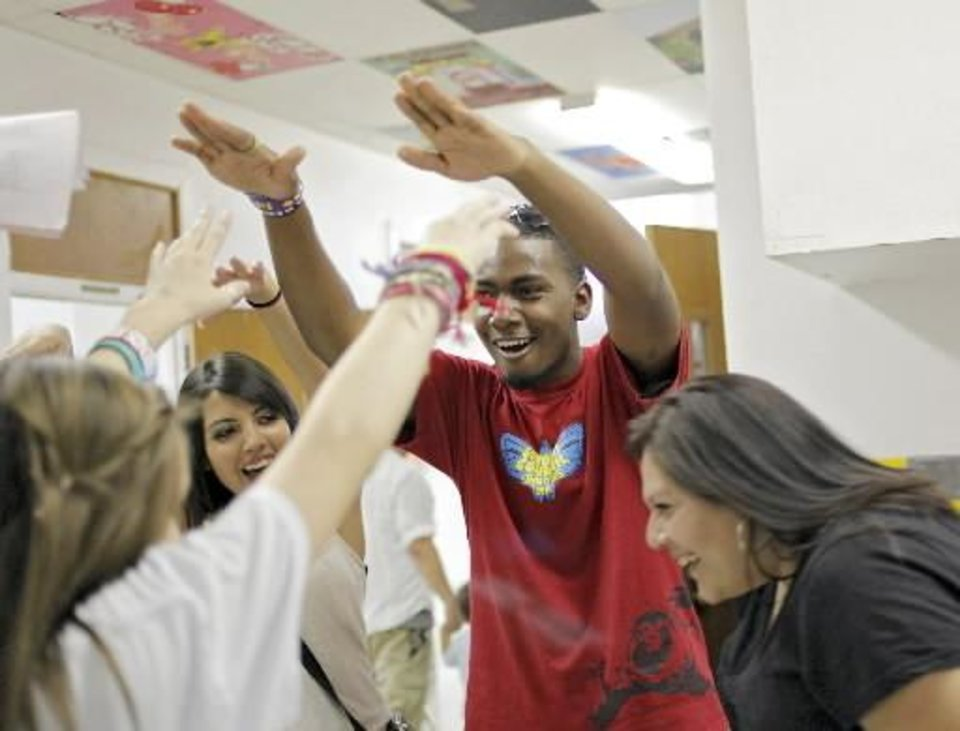 Photo - Student Council President Dimitri Wortham (center) and secretary Angie Mata (left) join other members of the student council to form a tunnel with their arms for parents and students to pass through as they are greeted at the front door during the Back 2 School Bash at Santa Fe South Charter High School in Oklahoma City on Monday, Aug. 1, 2011. Photo by John Clanton