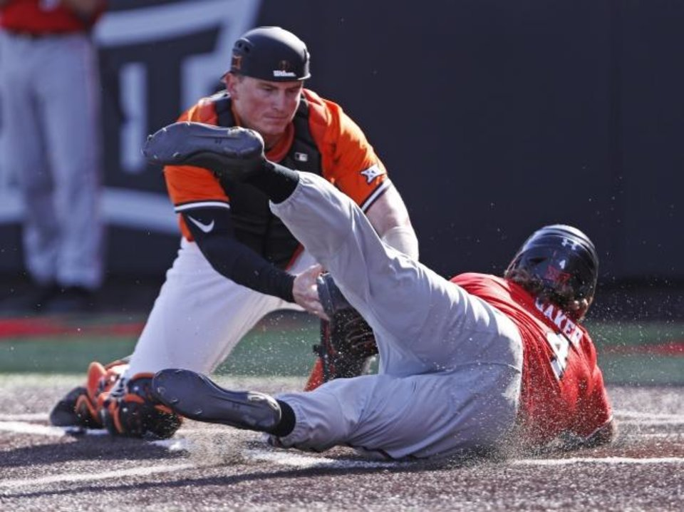 Photo -  Texas Tech's Dru Baker (4) slides safely into home plate around Oklahoma State's Bryce Carter during the third inning Saturday. [AP Photo/Brad Tollefson]
