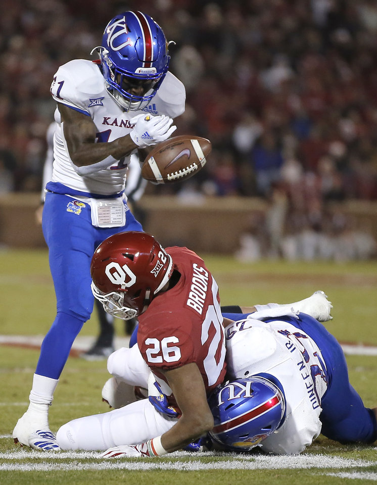 Photo - Kansas' Mike Lee (11) strips the ball from Oklahoma's Kennedy Brooks (26) as Joe Dineen Jr. (29) tries to bring him down during a college football game between the University of Oklahoma Sooners (OU) and the Kansas Jayhawks (KU) at Gaylord Family-Oklahoma Memorial Stadium in Norman, Okla., Saturday, Nov. 17, 2018. Photo by Bryan Terry, The Oklahoman