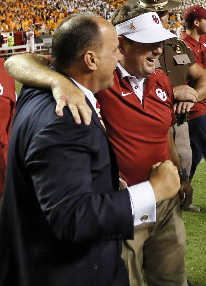 Photo - OU athletic director Joe Castiglione, left, and head coach Bob Stoops celebrate after the college football game between the Oklahoma Sooners (OU) and the Tennessee Volunteers at Neyland Stadium in Knoxville, Tennessee, Saturday, Sept. 12, 2015. OU won 31-24 in double overtime. Photo by Nate Billings, The Oklahoman