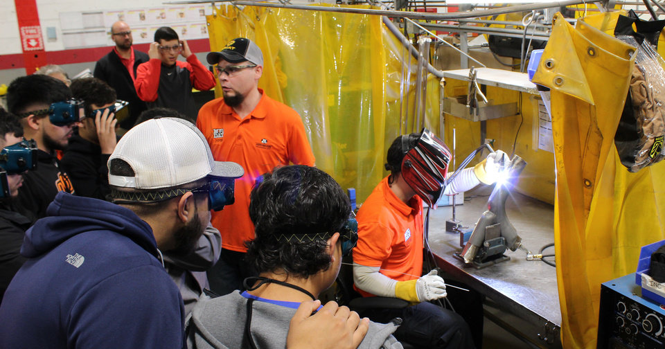 Photo -  Students from Santa Fe South, Tecumseh and Central Technology Center look on at WCC Aerobraze OKC, 4700 SE 59, as employees Erick Walling, standing, and Mohanad Alazzawi, welding, instruct and demonstrate TIG (tungsten inert gas) welding, earlier this year on Manufacturing Day. [PHOTO PROVIDED BY WCC AEROBRAZE OKC]