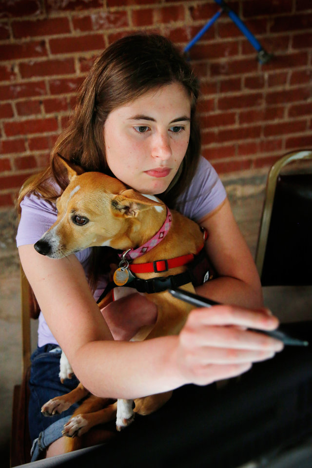 Photo -  Joy Lauffenburger holds Sophie, a service dog, while using her laptop to finish her art project. [Photo by Jim Beckel, The Oklahoman]