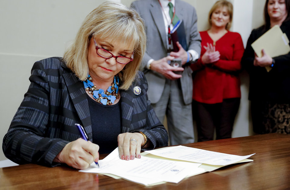 Photo -  Gov. Mary Fallin signs commutations on Wednesday for 21 Oklahoma inmates who were serving sentences of 10 years or longer for drug possession and other crimes that now carry lesser punishments. [Photo by Jim Beckel, The Oklahoman]