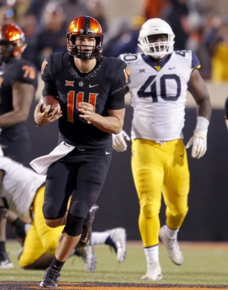 Photo - Oklahoma State's Taylor Cornelius (14) rushes in the fourth quarter during a college football game between the Oklahoma State Cowboys (OSU) and the West Virginia at Boone Pickens Stadium in Stillwater, Okla., Saturday, Nov. 17, 2018. OSU won 45-41.Photo by Sarah Phipps, The Oklahoman
