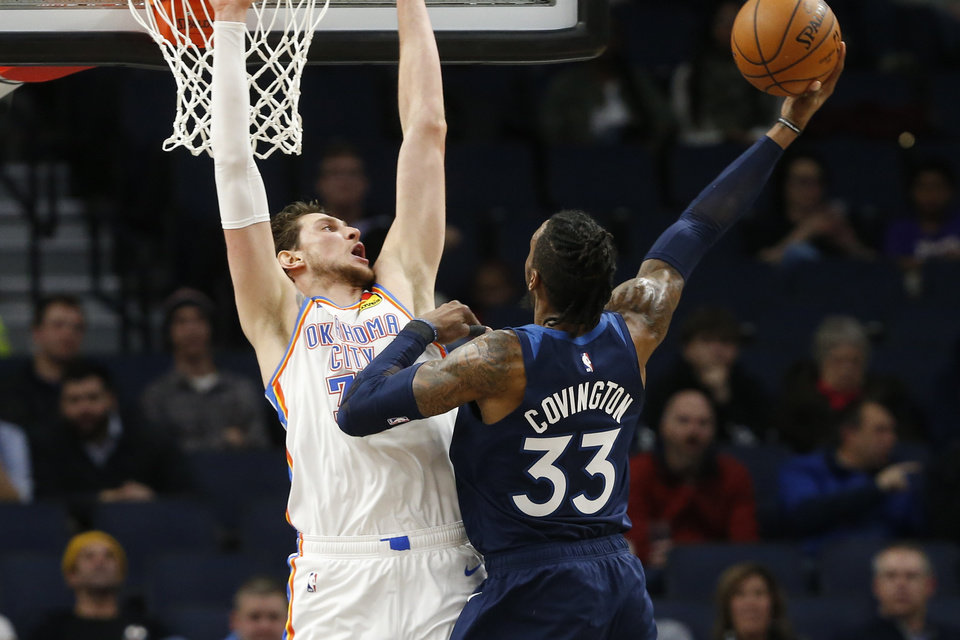 Photo - Minnesota Timberwolves' Robert Covington, right, shoots as Oklahoma City Thunder's Mike Muscala defends in the second half of an NBA basketball game Monday, Jan. 13, 2020, in Minneapolis. The Thunder won 117-104. Covington had 18 points for the Timberwolves. (AP Photo/Jim Mone)
