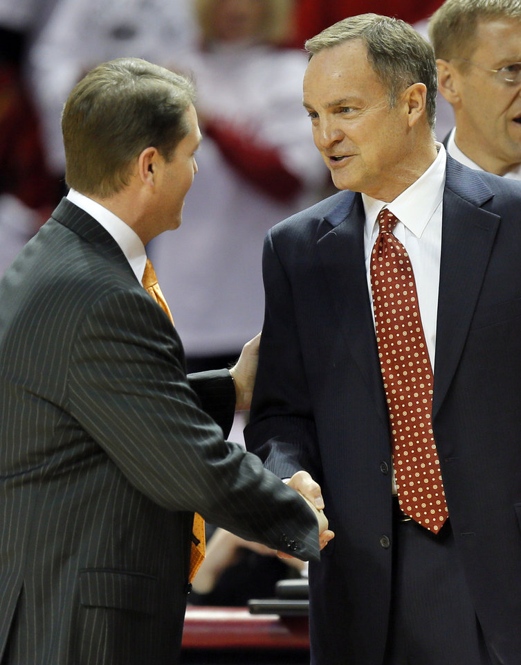 Photo - OSU coach Travis Ford, left, and OU coach Lon Kruger shake hands before the NCAA men's Bedlam basketball game between the Oklahoma State Cowboys (OSU) and the Oklahoma Sooners (OU) at Lloyd Noble Center in Norman, Okla., Monday, Jan. 27, 2014. Photo by Nate Billings, The Oklahoman