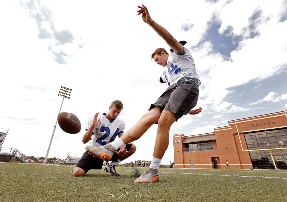 Photo -  Newcastle kicker Hunter Everett kicks before practice Wednesday with senior Brett Thomas, his holder. [PHOTO BY STEVE SISNEY, THE OKLAHOMAN]