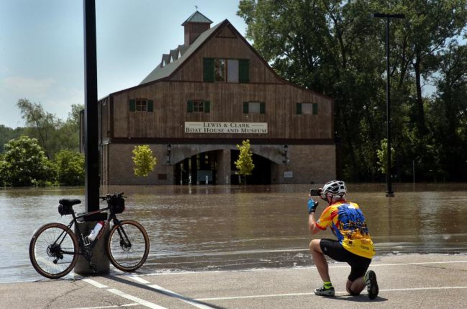 Photo - Andy Gaul of Tucson, Arizona photographs his bike in front of the flooded Lewis & Clark Boat House and Museum in Frontier Park on Friday, May 24, 2019. St. Charles officials closed the park and the Katy Trail due to Missouri River flooding, moving a weekend Irish Fest to New Town St. Charles. (Robert Cohen/St. Louis Post-Dispatch via AP)