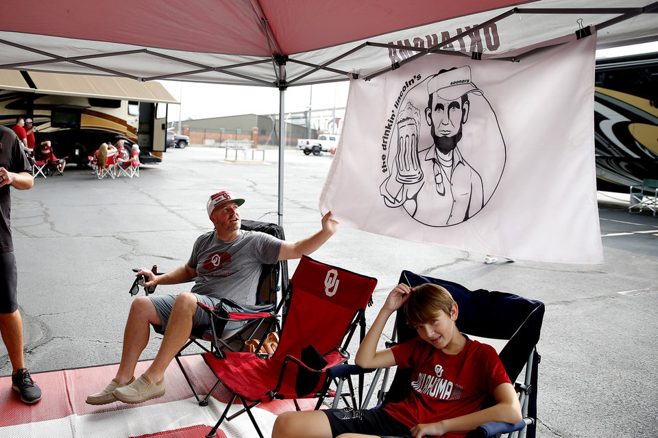 Photo - Randy Kornele shows his flag beside Braxton Walden, 13, as they sit outside before a college football game between the University of Oklahoma Sooners (OU) and Missouri State in Norman, Okla., Saturday, Sept. 12, 2020. [Bryan Terry/The Oklahoman]
