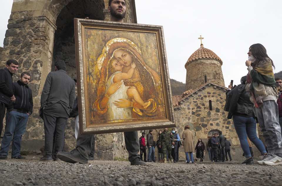 Photo -  A man holds an icon from the Dadivank, an Armenian Apostolic Church monastery dating to the 9th century, as ethnic Armenians leave the separatist region of Nagorno-Karabakh to Armenia, Saturday, Nov. 14, 2020. The territory is to be turned over to Azerbaijan on Sunday as part of territorial concessions in an agreement to end six weeks of intense fighting with Armenian forces. Hundreds of thousands of Azeris were displaced by the war that ended in 1994. It is unclear when any civilians might try to settle in Karvachar — which will now be known by its Azeri name Kalbajar — or elsewhere. (AP Photo/Dmitry Lovetsky)