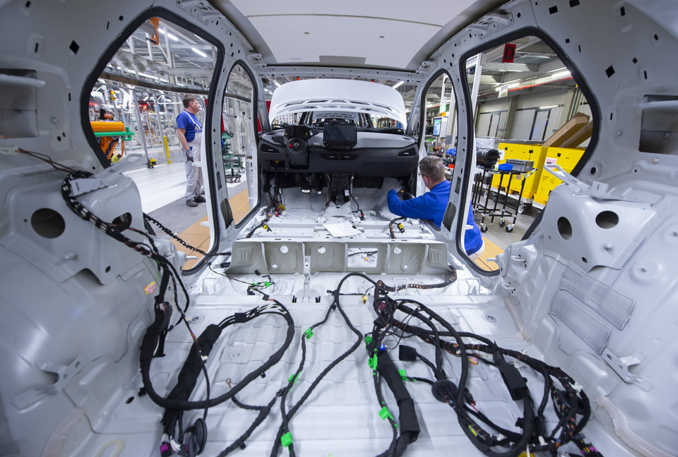 Photo -  FILE - In this Tuesday, Feb. 25, 2020 file photo, a worker completes an electric car ID.3 body at the assembly line, during a press tour at the plant of the German manufacturer Volkswagen AG, VW, in Zwickau, Germany. Automaker Volkswagen tripled sales of battery-only cars last year as its new electric compact ID.3 came on the market ahead of tough new limits on auto emissions. (AP Photo/Jens Meyer, file)