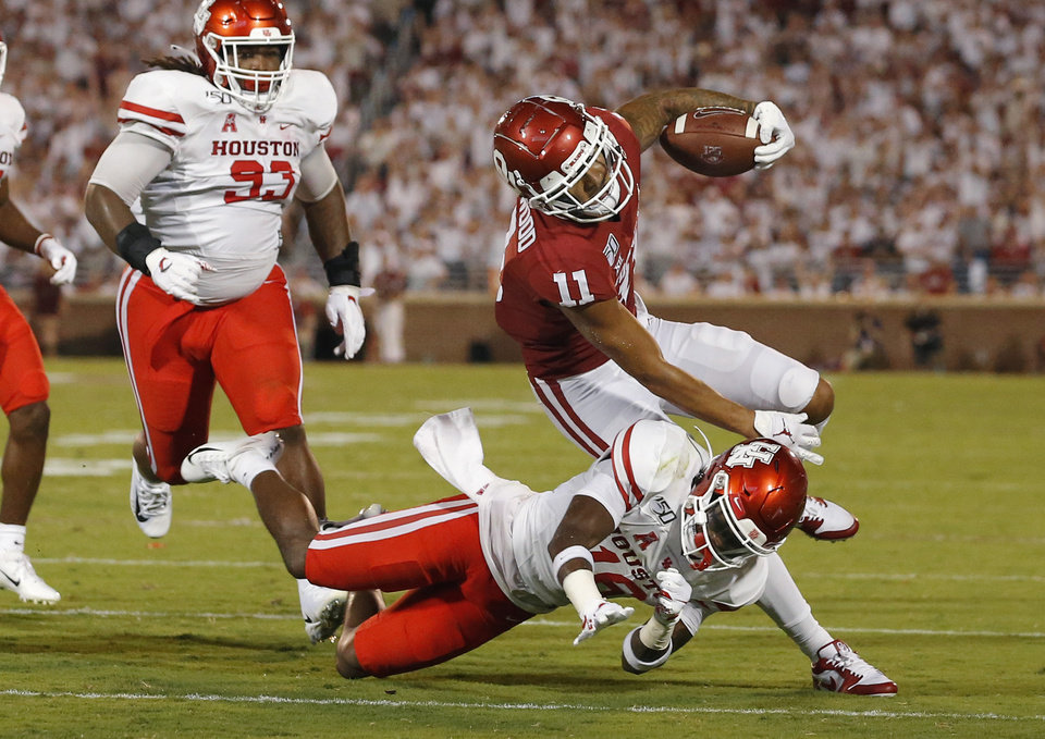 Photo - Oklahoma's Jadon Haselwood (11) is brought down by Houston's Ka'Darian Smith (16) during a college football game between the University of Oklahoma Sooners (OU) and the Houston Cougars at Gaylord Family-Oklahoma Memorial Stadium in Norman, Okla., Sunday, Sept. 1, 2019. Oklahoma won 49-31. [Bryan Terry/The Oklahoman]