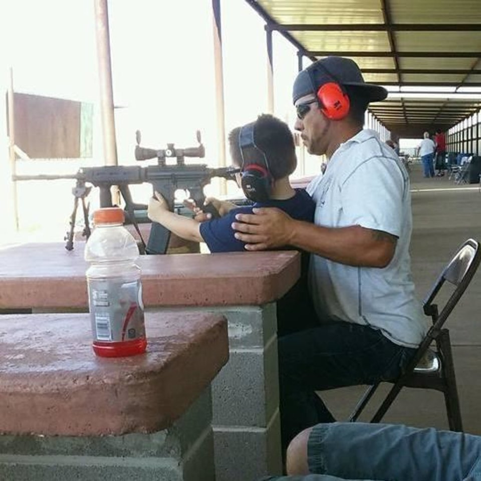 Photo -  In this photo from his Facebook page, Michael Dale Vance Jr. shows a boy how to shoot.