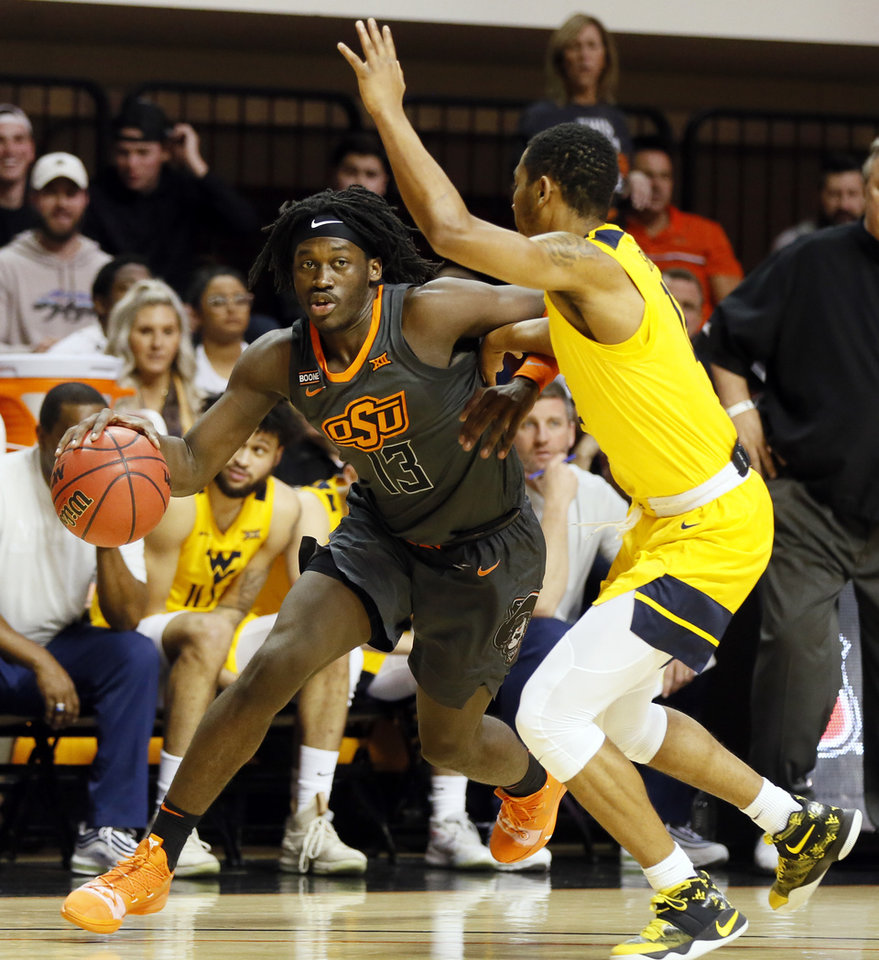 Photo - Oklahoma State's Isaac Likekele (13) drives against West Virginia's Taz Sherman (12) in the first half during a men's college basketball game between the Oklahoma State Cowboys and West Virginia Mountaineers at Gallagher-Iba Arena in Stillwater, Okla., Monday, Jan. 6, 2020. [Nate Billings/The Oklahoman]