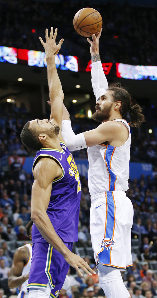 Photo - Oklahoma City's Steven Adams (12) shoots over Utah's Rudy Gobert (27) during an NBA basketball game between the Utah Jazz and the Oklahoma City Thunder at Chesapeake Energy Arena in Oklahoma City, Monday, Dec. 10, 2018. Oklahoma City won 122-113. Photo by Nate Billings, The Oklahoman