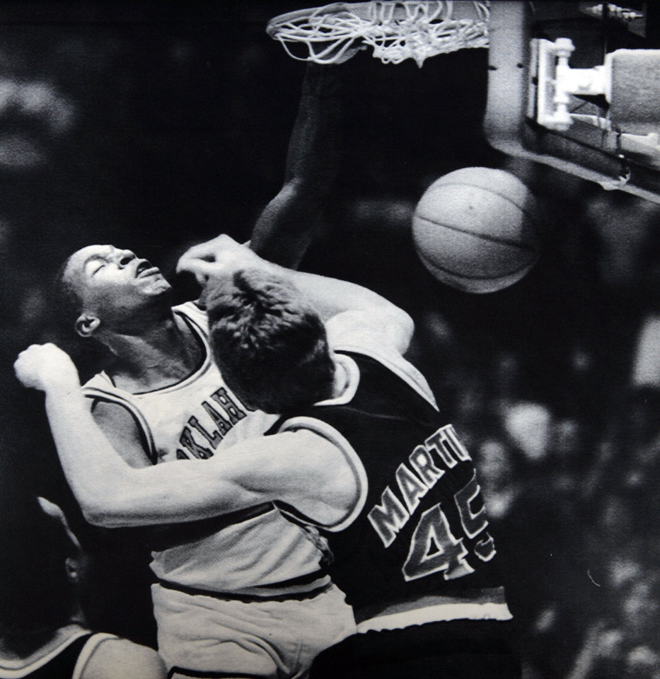 Photo - Former OU basketball player Wayman Tisdale. Even in the face of close defense by Kansas' Brian Martin, OU's Wayman Tisdale slams through two of his 28 points in the first half of the Sooners' 103-84 victory on Tuesday. (AP LaserPhoto) Photo taken unknown, Photo published 2/1/1984 in The Daily Oklahoman. ORG XMIT: KOD
