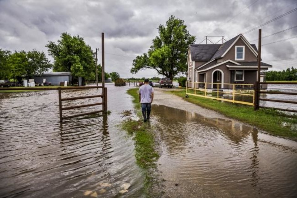 Photo -  Jose Menjibar checks the flood damage to his property Tuesday as he walks through the water after heavy rains flooded areas in El Reno. [Chris Landsberger/The Oklahoman]