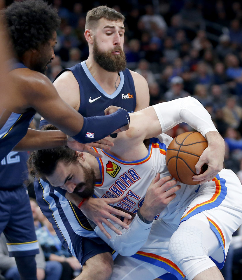 Photo - Oklahoma City's Steven Adams (12) gains control of the ball under Memphis' Jonas Valanciunas (17) during an NBA basketball game between the Oklahoma City Thunder and the Memphis Grizzlies at Chesapeake Energy Arena in Oklahoma City, Wednesday, Dec. 18, 2019. Oklahoma City won 126-122. [Bryan Terry/The Oklahoman]