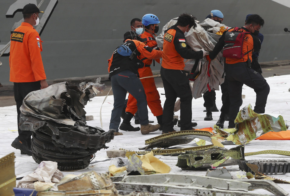 Photo -  Rescuers carry debris found in the waters around the location where Sriwijaya Air passenger jet crashed at Tanjung Priok Port in Jakarta, Indonesia, Monday, Jan. 11, 2021. The search for the black boxes of a crashed Sriwijaya Air jet has intensified to boost the investigation into what caused the plane carrying dozens of people to nosedive into Indonesia seas. The Boeing 737-500 jet disappeared during heavy rain on Saturday.  (AP Photo/Achmad Ibrahim)