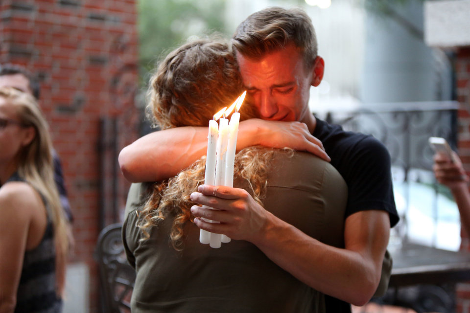 Photo - FILE - In this Sunday, June 12, 2016 file photo, Brett Morian hugs an fellow mourner during a candlelight vigil for those killed at the Pulse nightclub in Orlando, Fla. The worst mass shooting in modern U.S. history unfolded on Latin Night at the gay nightclub. The gunman, Omar Mateen, killed 49 people over the course of three hours before dying in a shootout with SWAT team members. During the standoff, he pledged allegiance to the Islamic State. (Joshua Lim/Orlando Sentinel via AP)
