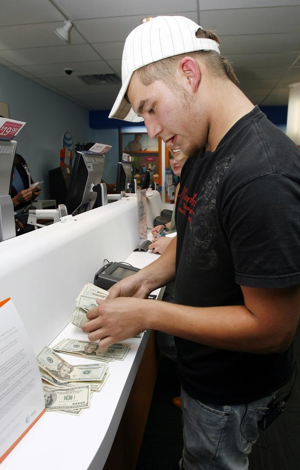 Photo - Mike Balliet counts out $704 in cash for an 8GB iPhone and accessories as the first person to buy an iPhone at the AT&T store at 6959 NW Expressway in Oklahoma City, Friday, June 29, 2007. [THE OKLAHOMAN ARCHIVES]