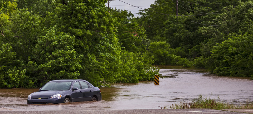 Photo - A car is stranded in flood waters on Banner Rd. in El Reno, Okla. after heavy rains flooded the area on Monday, May 20, 2019.  [Chris Landsberger/The Oklahoman]
