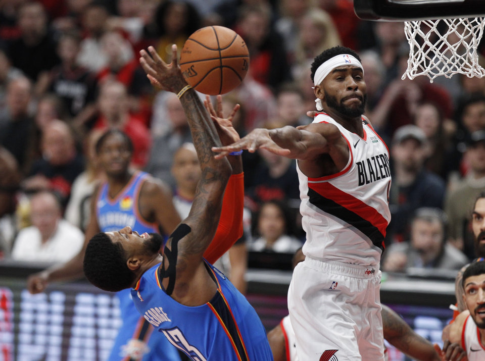 Photo - Portland Trail Blazers forward Maurice Harkless, right, blocks the shot of Oklahoma City Thunder forward Paul George, left, during the first half of Game 1 of a first-round NBA basketball playoff series in Portland, Ore., Sunday, April 14, 2019. (AP Photo/Steve Dipaola)