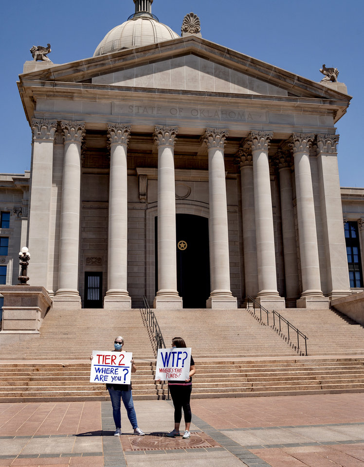 Photo - Diane and Alyssa Whisner, from left, carry signs as they gather with other self-employed Oklahomans at the Oklahoma state Capitol to protest the lack of unemployment payments on Monday, May 18, 2020, in Oklahoma City, Okla..  [Chris Landsberger/The Oklahoman]