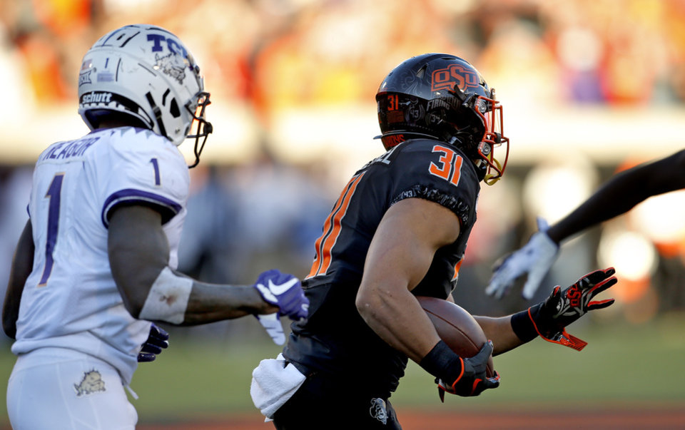 Photo - Oklahoma State's Kolby Harvell-Peel (31) returns an interception as TCU's Jalen Reagor (1) defends in the fourth quarter during the college football game between the Oklahoma State University Cowboys and the TCU Horned Frogs at Boone Pickens Stadium in Stillwater, Okla.,  Saturday, Nov. 2, 2019. OSU won 34-27. [Sarah Phipps/The Oklahoman]
