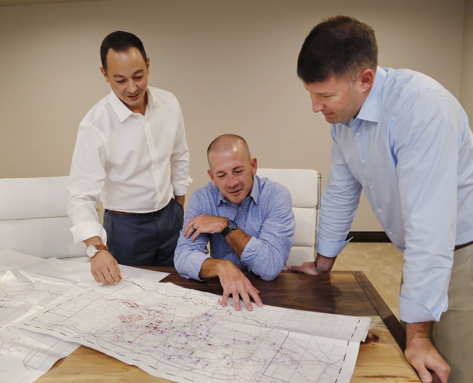Photo -  Valiant Midstream executives Brandon Webster, left, Chad Cagle and Zach Gray look over maps at their office in north Oklahoma City. [THE OKLAHOMAN ARCHIVES]