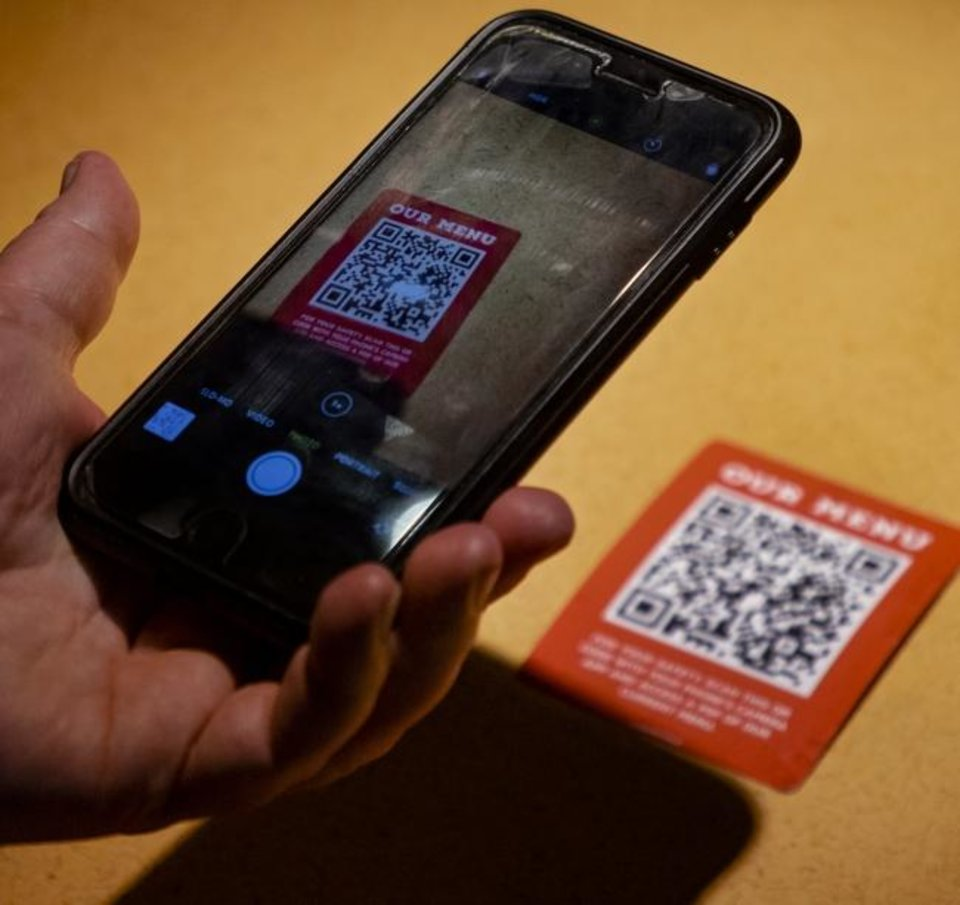 Photo -  Most mobile users also include data plans as part of their telecommunications packages. Here, a restaurant staff member demonstrates how customers can bring up the establishment's menu by scanning a QR code. [Chris Landsberger/The Oklahoman]