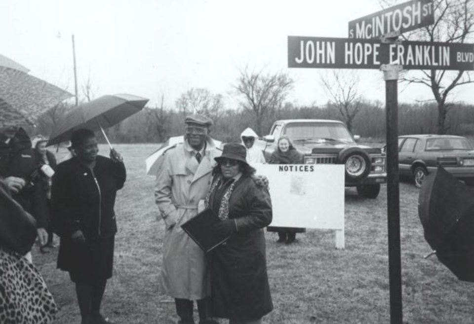 Photo -  John Hope Franklin, in the light-colored trench coat, stands near the sign for John Hope Franklin Boulevard in Rentiesville. [Larry O'Dell Collection, OHS]