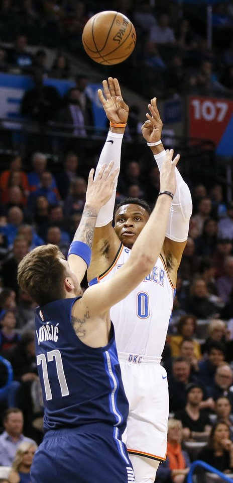 Photo - Oklahoma City's Russell Westbrook (0) shoots over Dallas' Luka Doncic (77) during an NBA basketball game between the Oklahoma City Thunder and Dallas Mavericks at Chesapeake Energy Arena in Oklahoma City, Monday, Dec. 31, 2018. Photo by Nate Billings, The Oklahoman