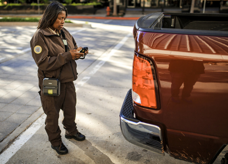 Photo -  Oklahoma City Police Service Technician Marsha Nealy writes a parking ticket along Main Street in downtown Oklahoma City. [Photo by Chris Landsberger, The Oklahoman]