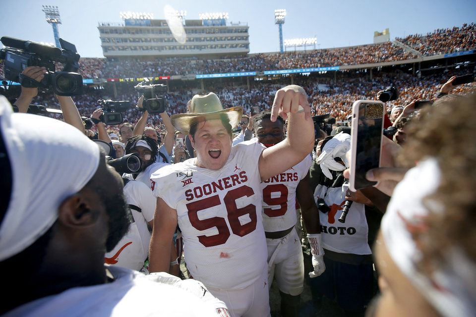 Photo - Oklahoma offensive lineman Creed Humphrey (56) gives the Horns Down as he celebrates with the Golden Hat after the Red River Showdown college football game between the University of Oklahoma Sooners (OU) and the Texas Longhorns (UT) at Cotton Bowl Stadium in Dallas, Saturday, Oct. 12, 2019. Oklahoma won 34-27. [Bryan Terry/The Oklahoman]