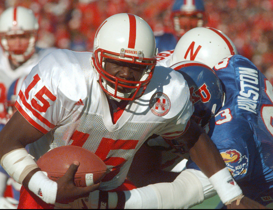 Photo - COLLEGE FOOTBALL: University of Nebraska quarterback Tommie Frazier (15) runs to inside the one yard line during the first quarter as Kansas defensive tackle Dewey Houston (83) tries to stop his progress Saturday, Nov. 11, 1995, in Lawrence, Kan. (AP Photo/Cliff Schiappa)