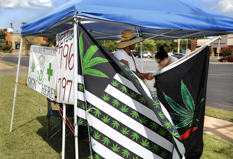 "Photo - A volunteer holds a flag Tuesday morning, Aug. 7, 2018, while a woman signs a petition requesting Oklahomans be given a chance to vote on the issue of recreational marijuana. The man was collecting signatures for SQ 796 and SQ 797 at this tent on Lindsey Street in Norman. He has been there for four days, he said.  He remained optimistic  about gathering signatures on the petitions, saying he ""would like to get 300 today."" Photo by Jim Beckel, The Oklahoman"
