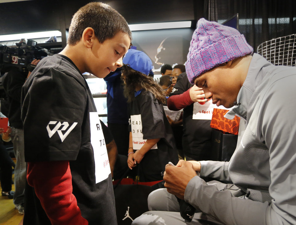 Photo - Joey Bustos, 10, from the Oklahoma County boys and Girls Clubs, watches  Russell Westbrook  sign his new shoes at the House of Hoops in Penn Square Mall, Wednesday, December 10, 2014. Photo by David McDaniel