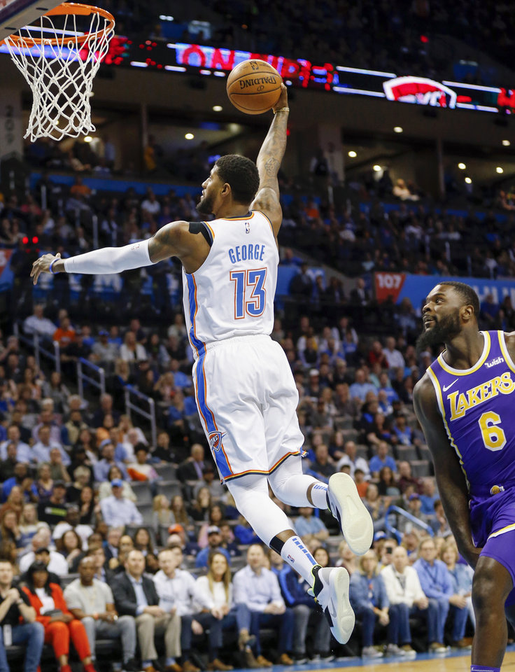 Photo - Oklahoma City's Paul George (13) dunks the ball in front of Los Angeles' Lance Stephenson (6) in the first quarter during an NBA basketball game between the Los Angeles Lakers and the Oklahoma City Thunder at Chesapeake Energy Arena in Oklahoma City, Tuesday, April 2, 2019. Photo by Nate Billings, The Oklahoman