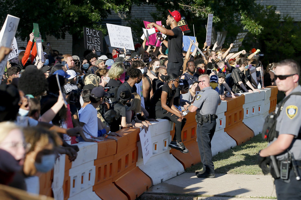 Photo - An Oklahoma City police officer talks with protesters outside police headquarters  in Oklahoma City on Sunday, May 31, 2020. The Black Lives Matter protest was in response to the death of George Floyd. [Bryan Terry/The Oklahoman]
