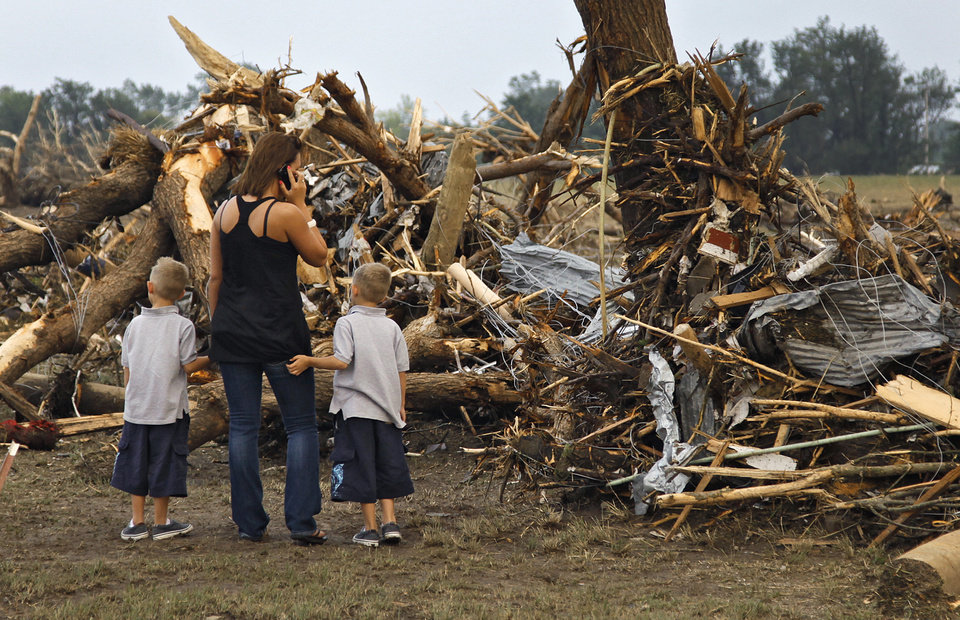 Photo - Kirby Easter and her sons Josh and Jacob try to find anything salvageable in the debris left behind after the home of Tom Chronister was destroyed north of El Reno, Tuesday, May 24, 2011. Photo by Chris Landsberger, The Oklahoman ORG XMIT: KOD
