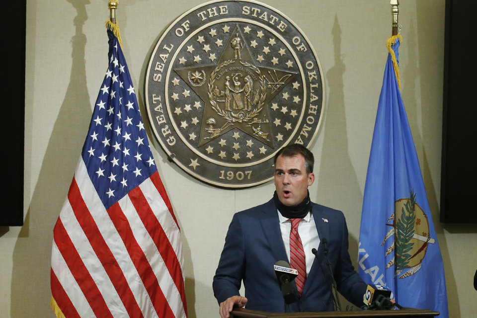 Photo - Oklahoma Gov. Kevin Stitt gestures as he speaks during a news conference, Tuesday, June 30, 2020, in Oklahoma City. With his face mask down around his neck, Stitt encouraged Oklahomans to wear a face mask, but said that he will not consider placing a face mask mandate on Oklahoma. (AP Photo/Sue Ogrocki)