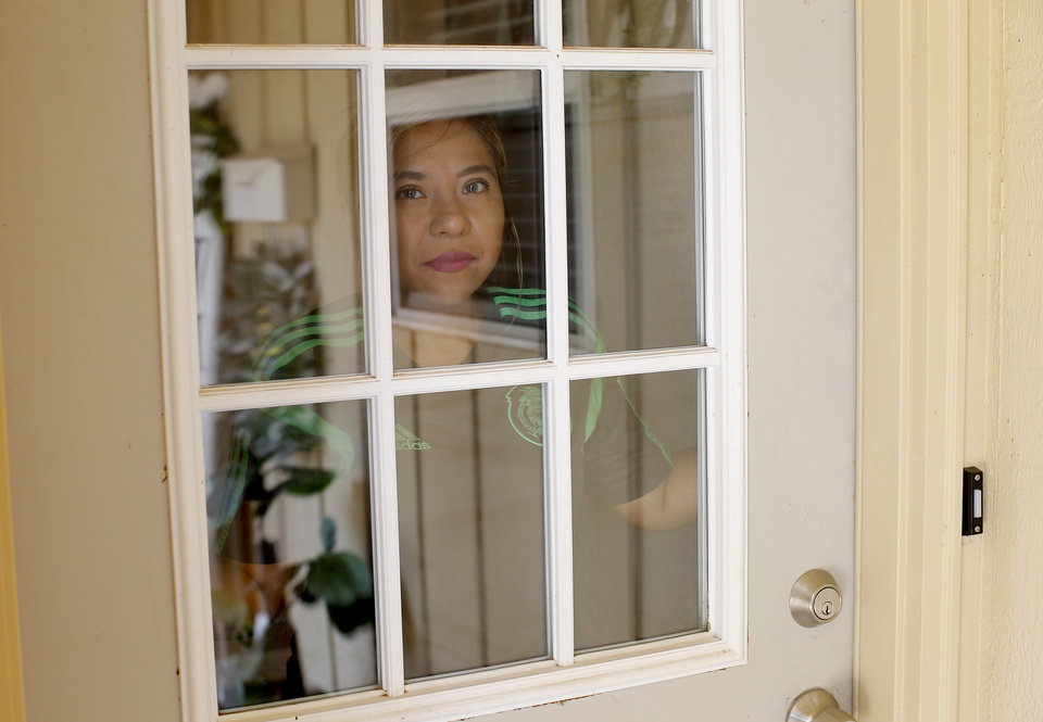 Photo -  Jess Olivo, who was diagnosed with COVID-19 and has recovered, looks out through the door to her home in the Warr Acres area on Friday. Five other members of Olivo's family contracted COVID-19 amid a surge of cases among Oklahoma City's Latino community. [Bryan Terry/The Oklahoman]